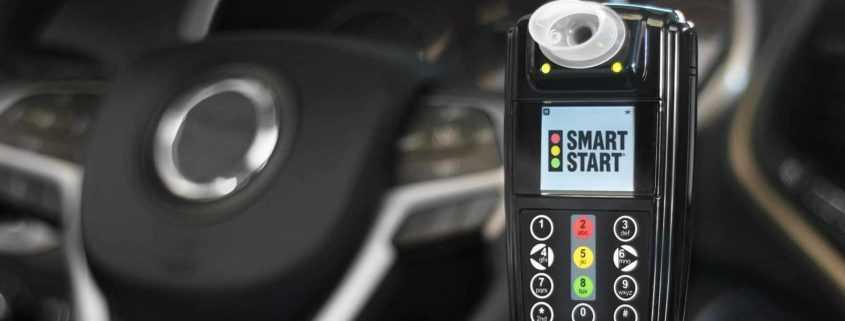 Customer holding a Smart Start Ignition Interlock Device in car