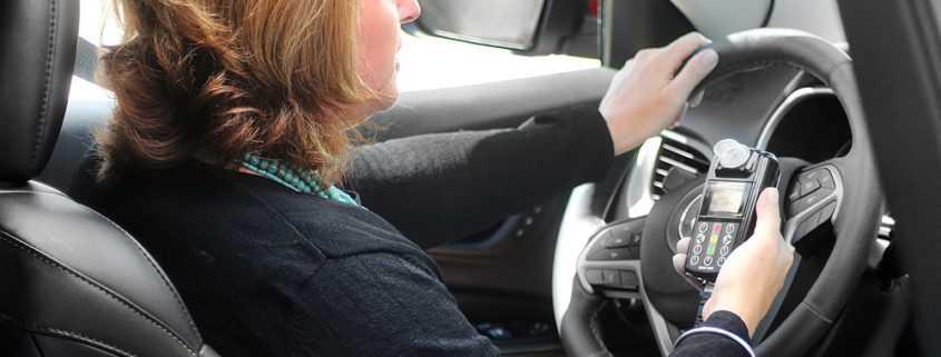Customer holding an Ignition Interlock Device in car