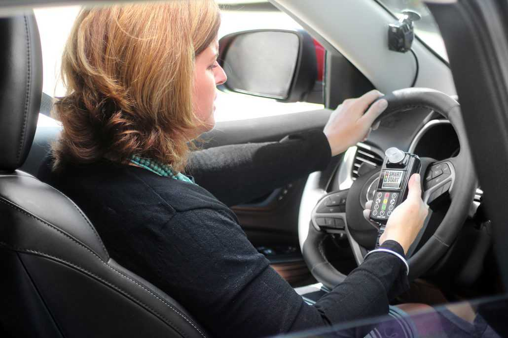 Customer holding an Ignition Interlock Device in car with camera