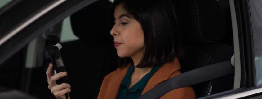 A woman driver prepares to blow into a car breathalyzer