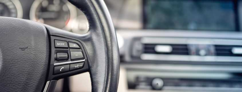 Vehicle steering wheel with details of buttons and adjustment controls in background
