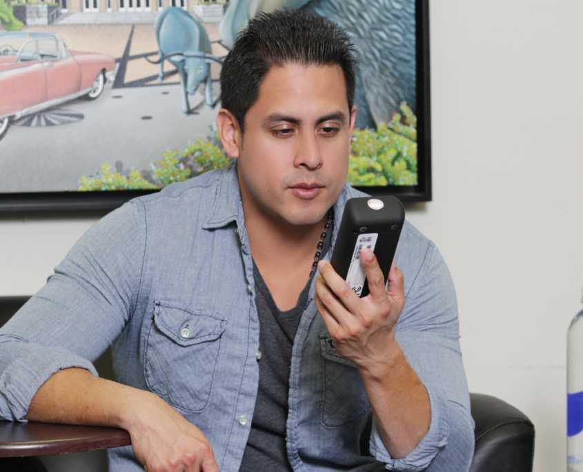 Photo of Man Holding SMART Mobile Device in a Room