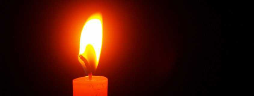 Candle burning brightly at candlelight vigil