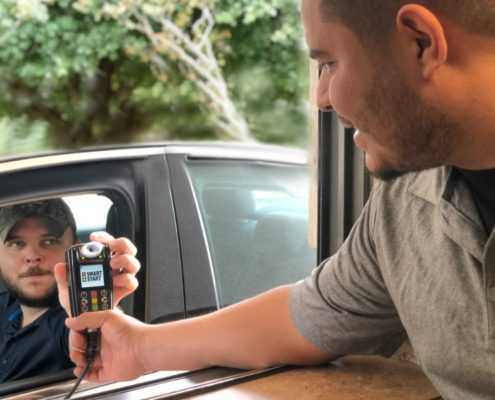 Technician hands Ignition Interlock Device to a satisfied customer.