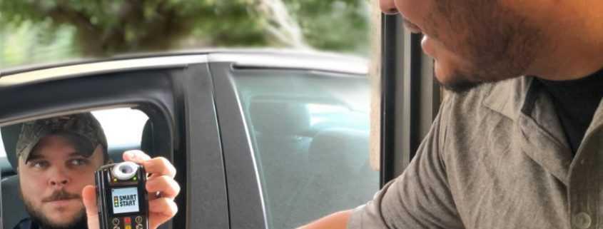 Smart Start Technician hands Ignition Interlock Device customer in car