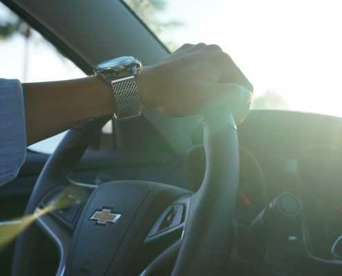 male with hand on steering wheel of vehicle