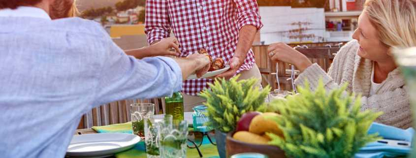 A Labor Day party host feeds guests at a cookout.
