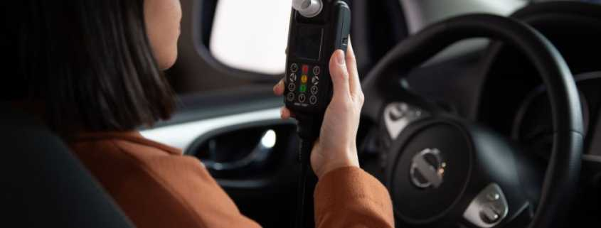 A woman uses a Smart Start Ignition Interlock Device before starting her car.