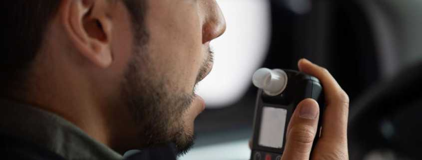 Driver getting ready to blow into Smart Start Ignition Interlock Device