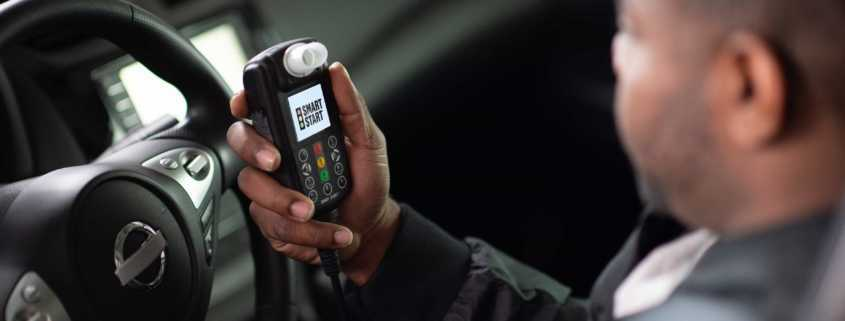 A man in a car views Ignition Interlock Device test results