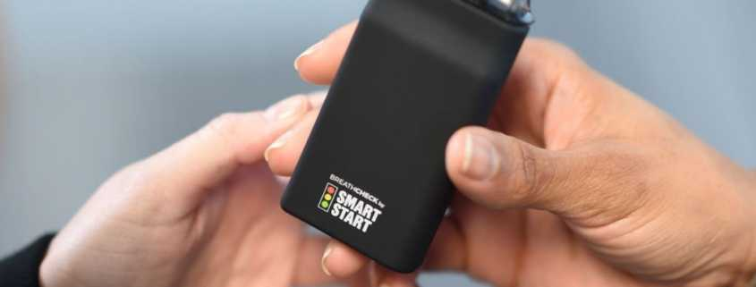 BreathCheck portable alcohol breathalyzer is handed to another person